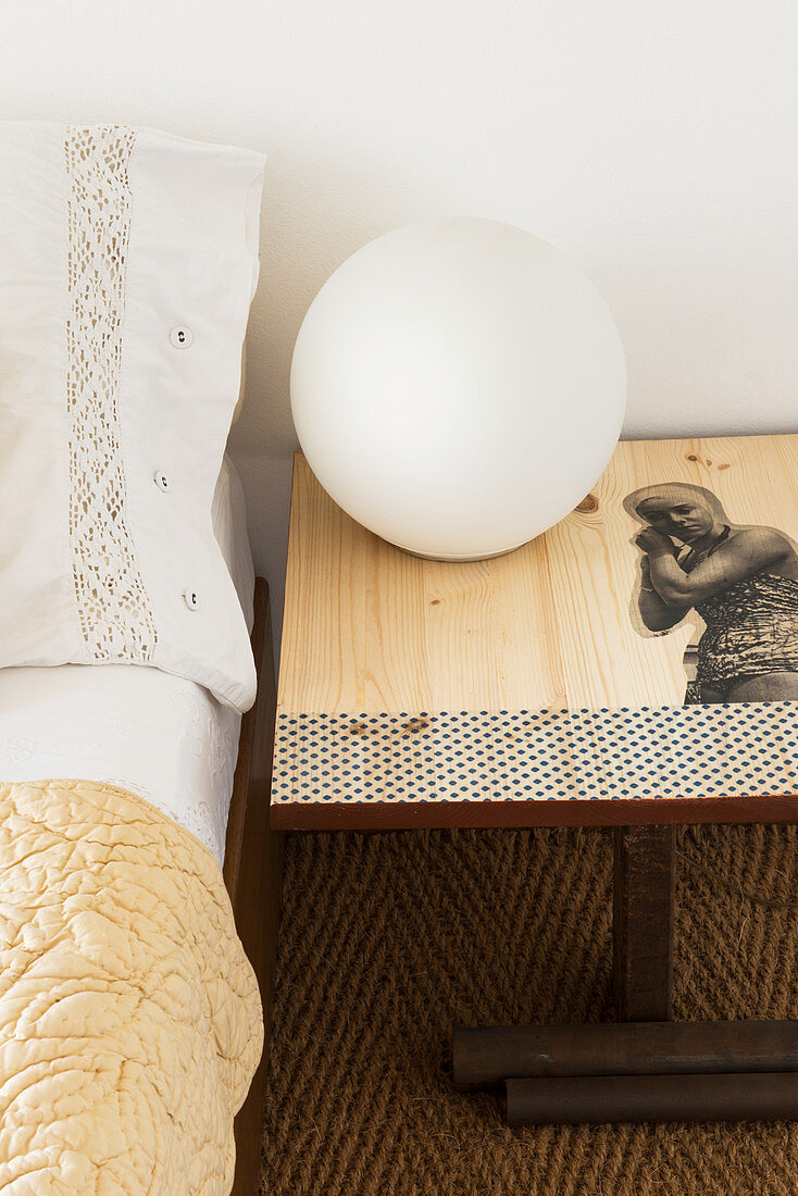 Spherical lamp on bedside table decorated with decoupage motif
