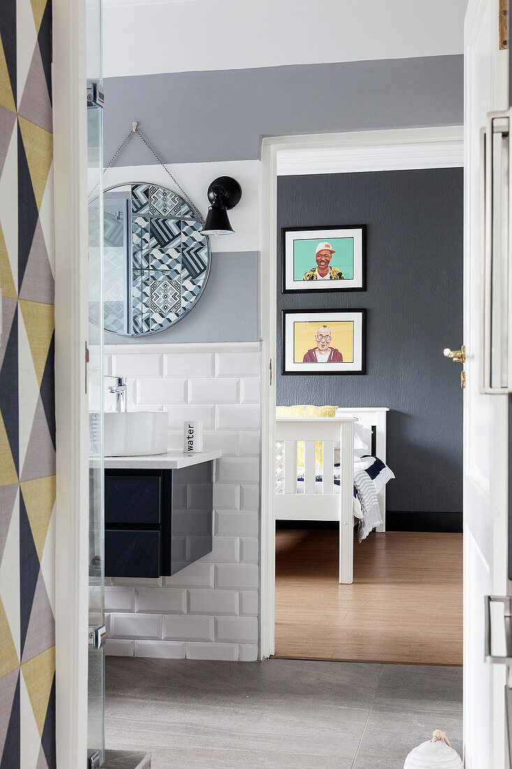 Washstand with countertop sink on subway tiles below round mirror in bathroom with view into bedroom