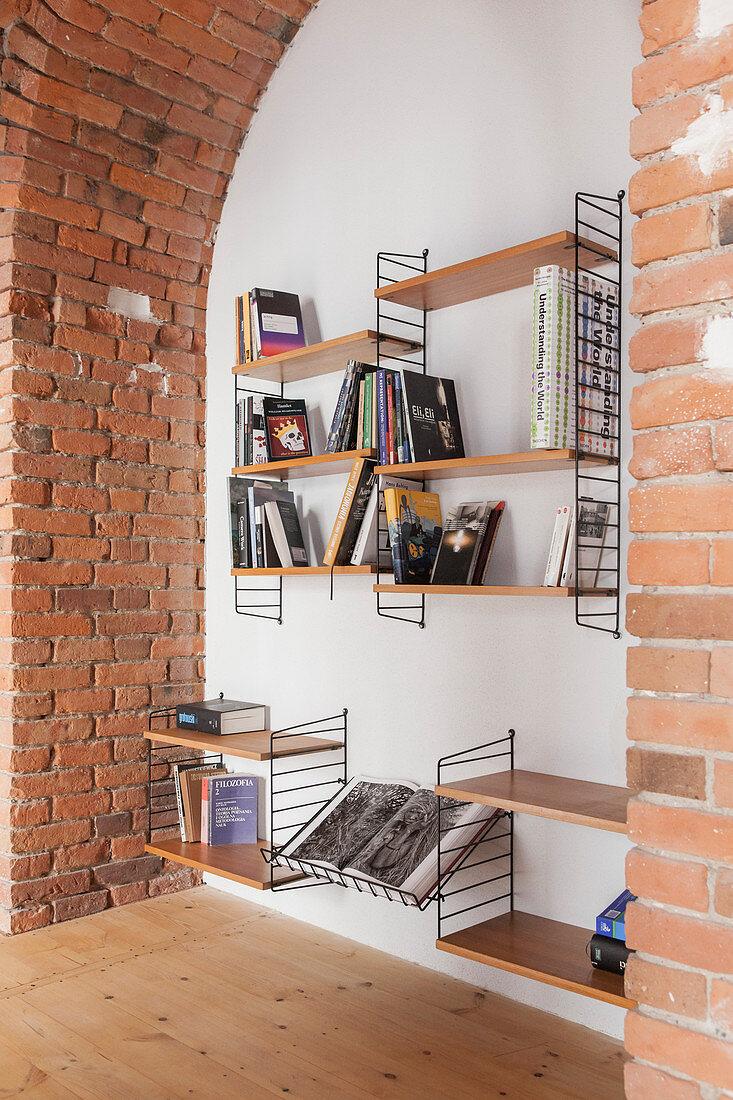 Books on String shelves in niche below brick arch