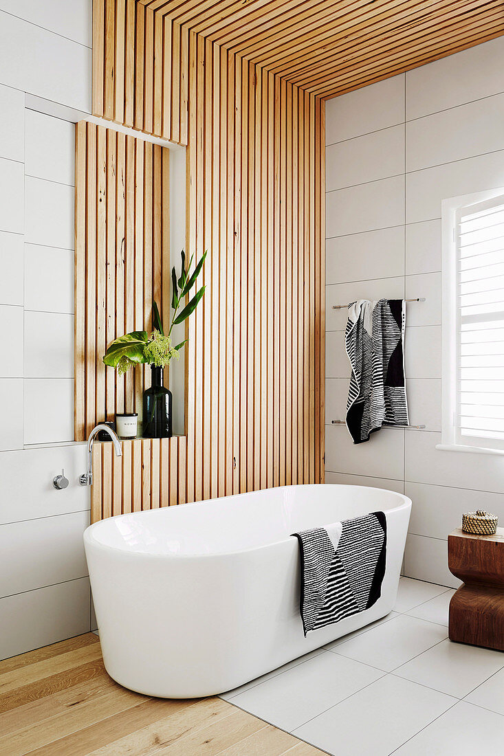 Freestanding bathtub in front of wooden paneling in the bathroom