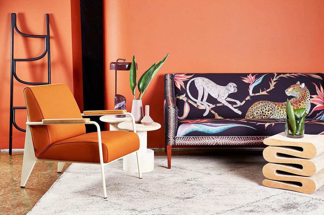 Designer-Sofa in Afrika-Look, Beistelltisch, Leiter, Armlehnstuhl und Couchtisch im Wohnzimmer mit orangefarbener Wand
