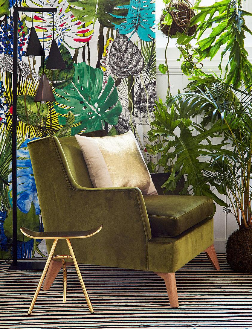 Gilt stool and green velvet armchair in front of leaf-patterned wallpaper