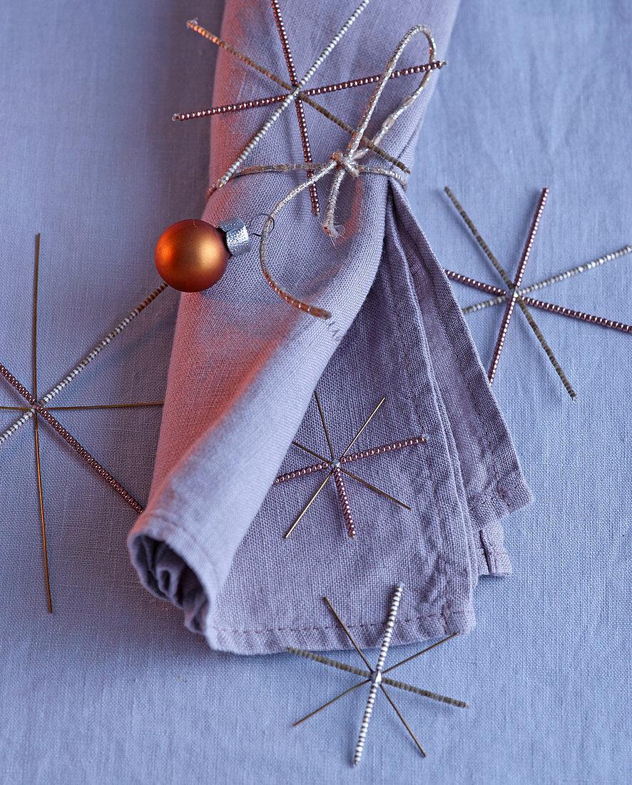 Weihnachtsdeko mit Stoffserviette, Silbersternen und kupferfarbener Christbaumkugel