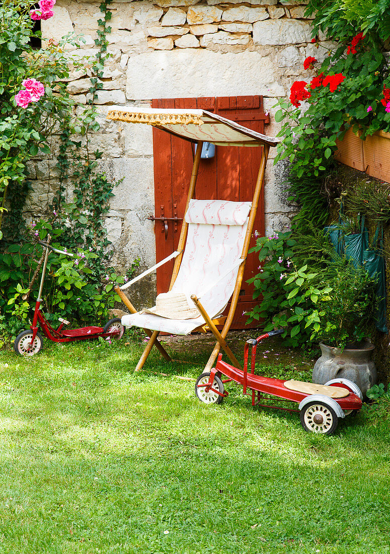 Deckchair and old toys on lawn outside stone house