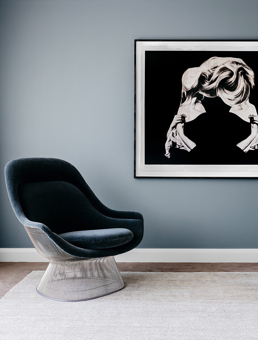 Upholstered armchair in front of large-format photography on gray wall in bedroom