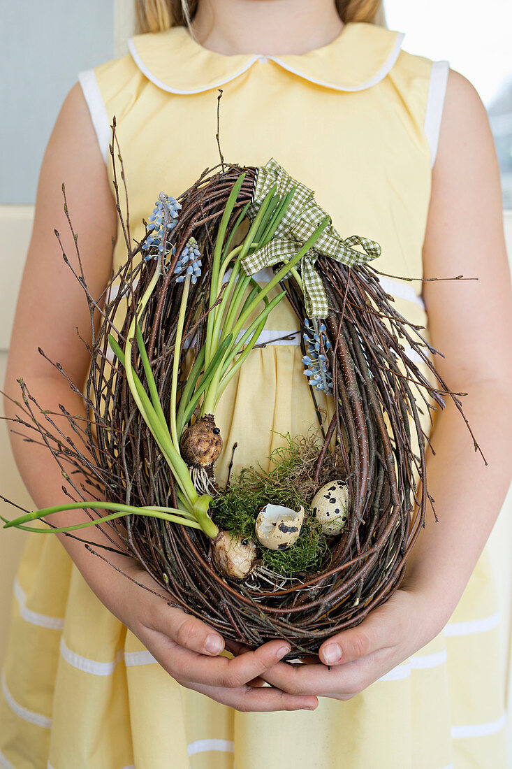 Girl holding egg-shaped Easter wreath with grape hyacinths and quail eggs