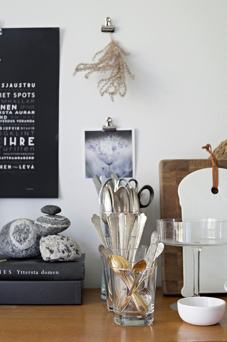 Kitchen utensils, cutlery in glasses, books and pebbles on wooden worksurface