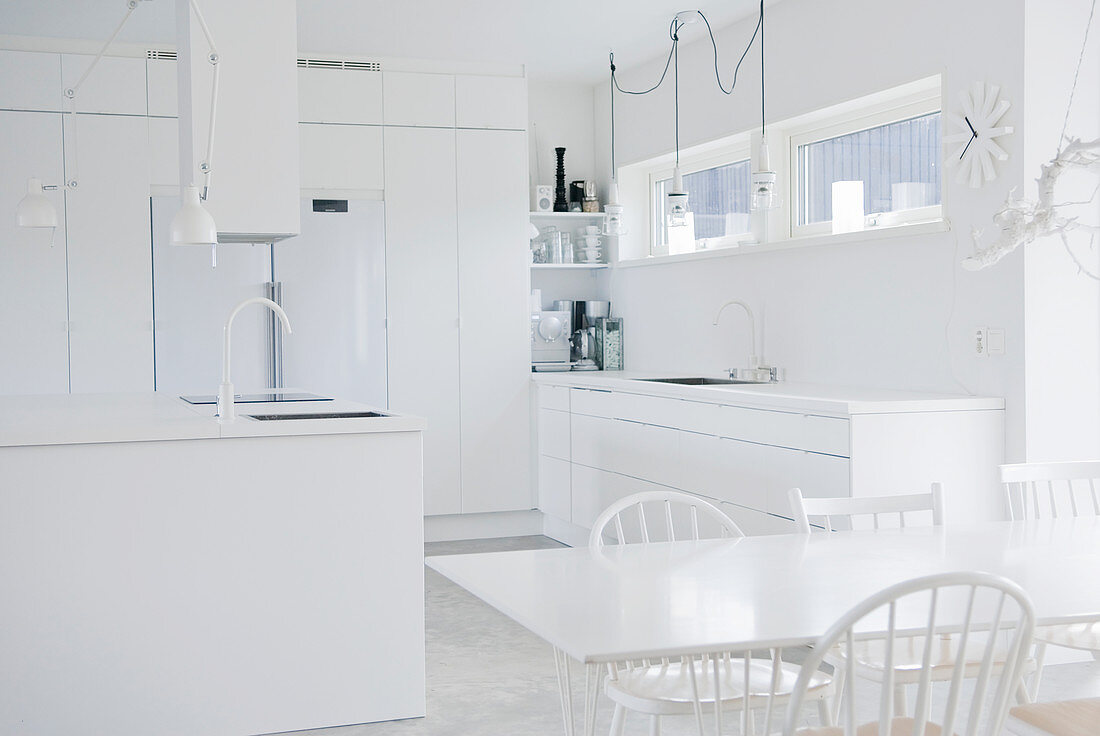 Dining table and island counter in completely white kitchen