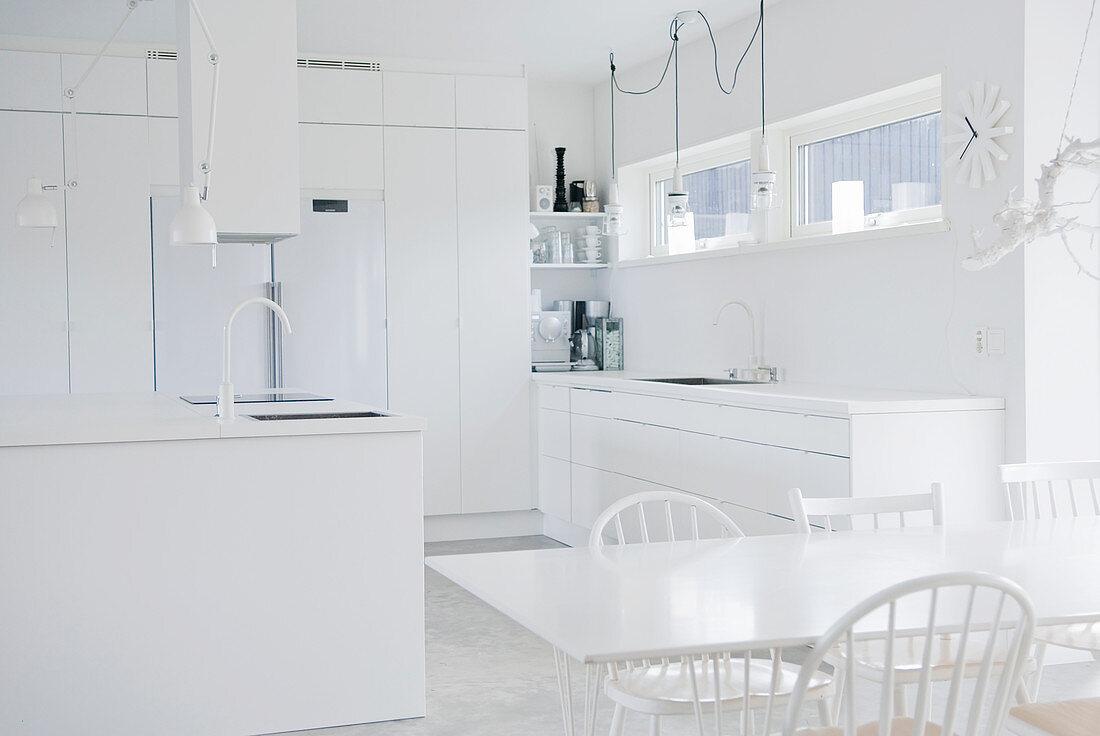 Küche ganz in Weiß mit Esstisch und Kochinsel