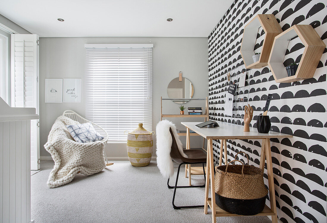 Black and white wallpaper, desk, chair and blanket on armchair in study
