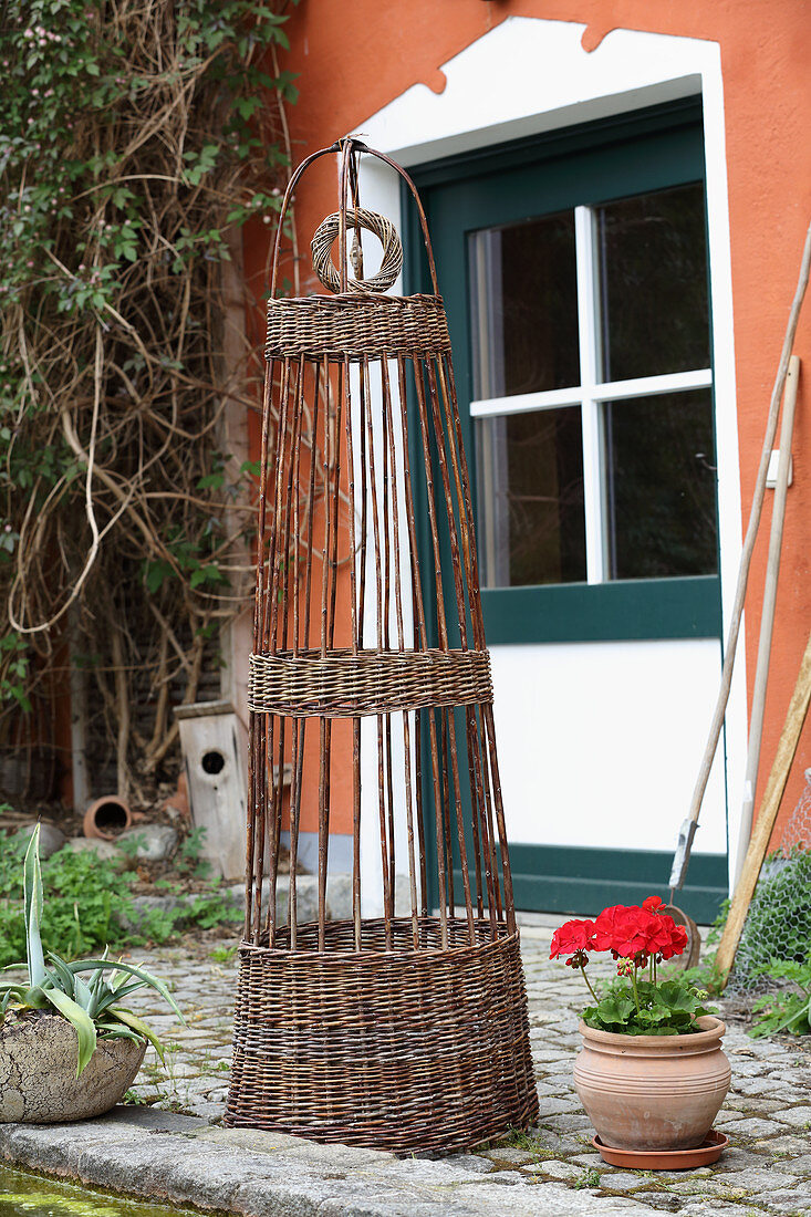 Decorative wicker obelisk outside house
