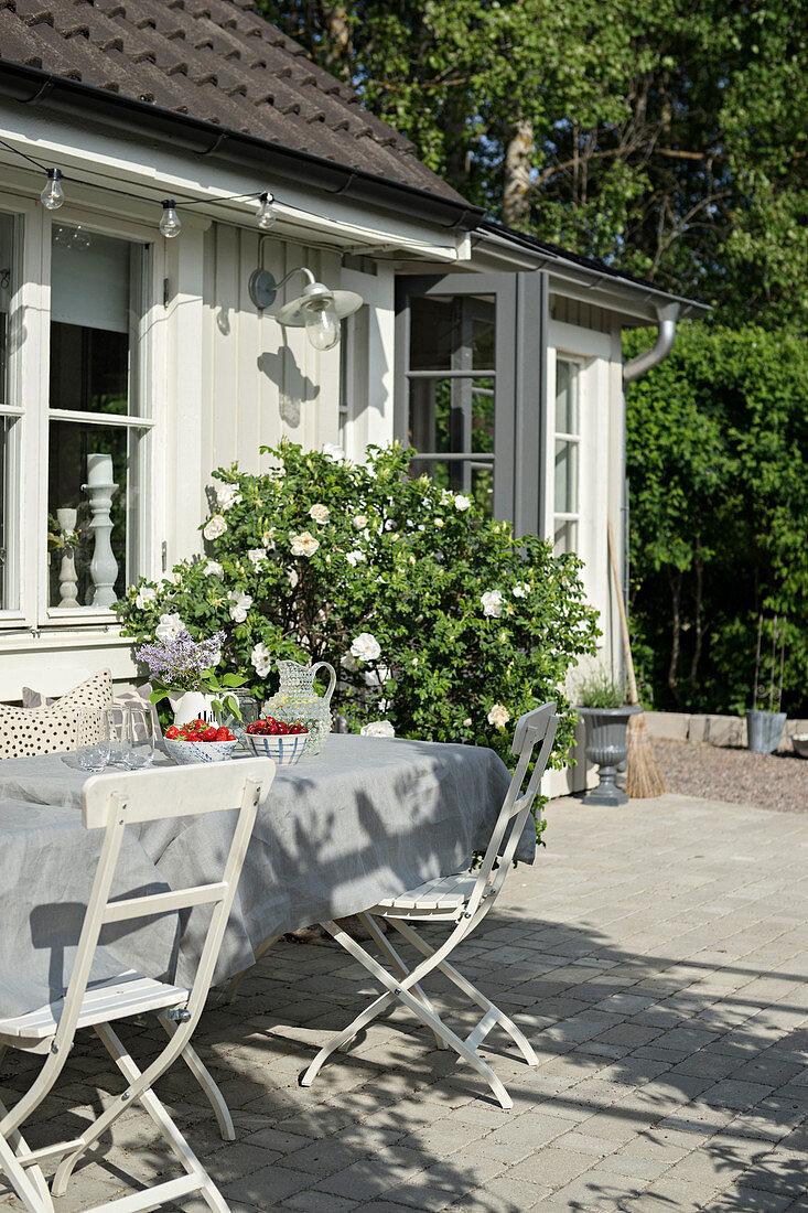Gartentisch auf der Terrasse vor dem weißen Schwedenhaus