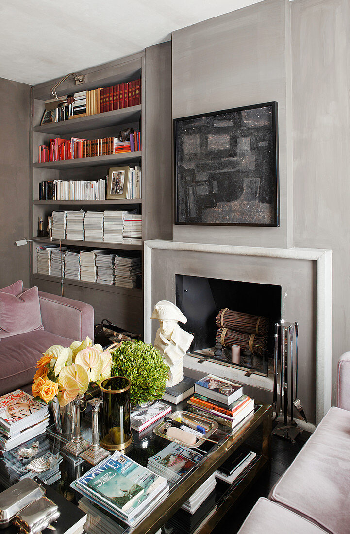 Coffee table in front of open fireplace and fitted shelves in grey wall