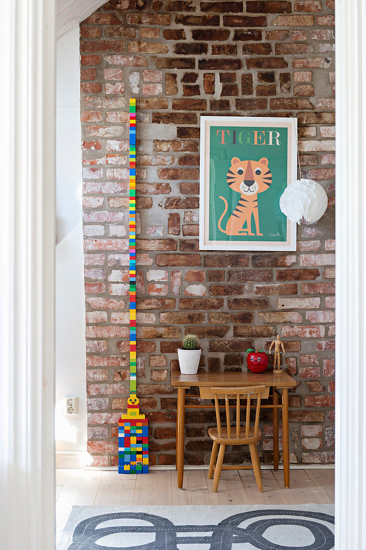 Old child's table and chair below picture of tiger on brick wall