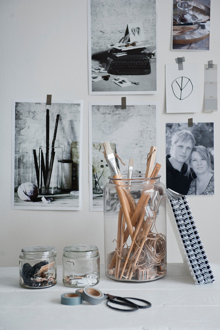 Office utensils in glass jars in front of black and white photos on wall