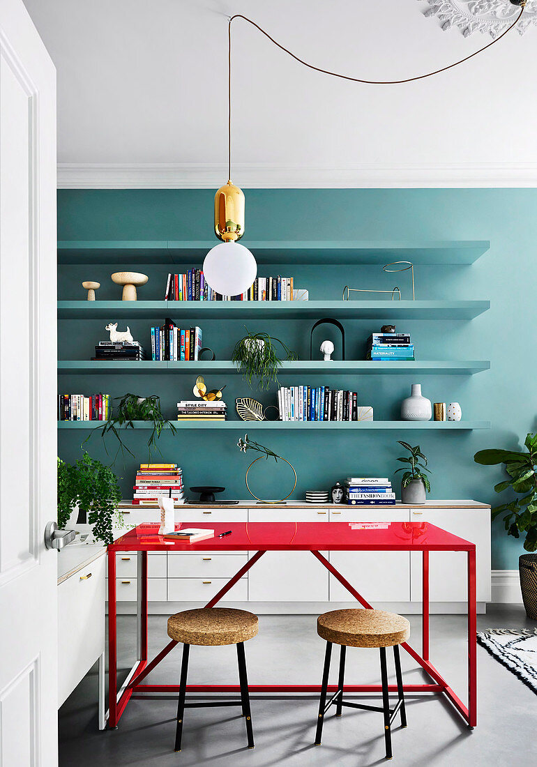 Red table with two stools and shelves on a petrol-colored wall in the study