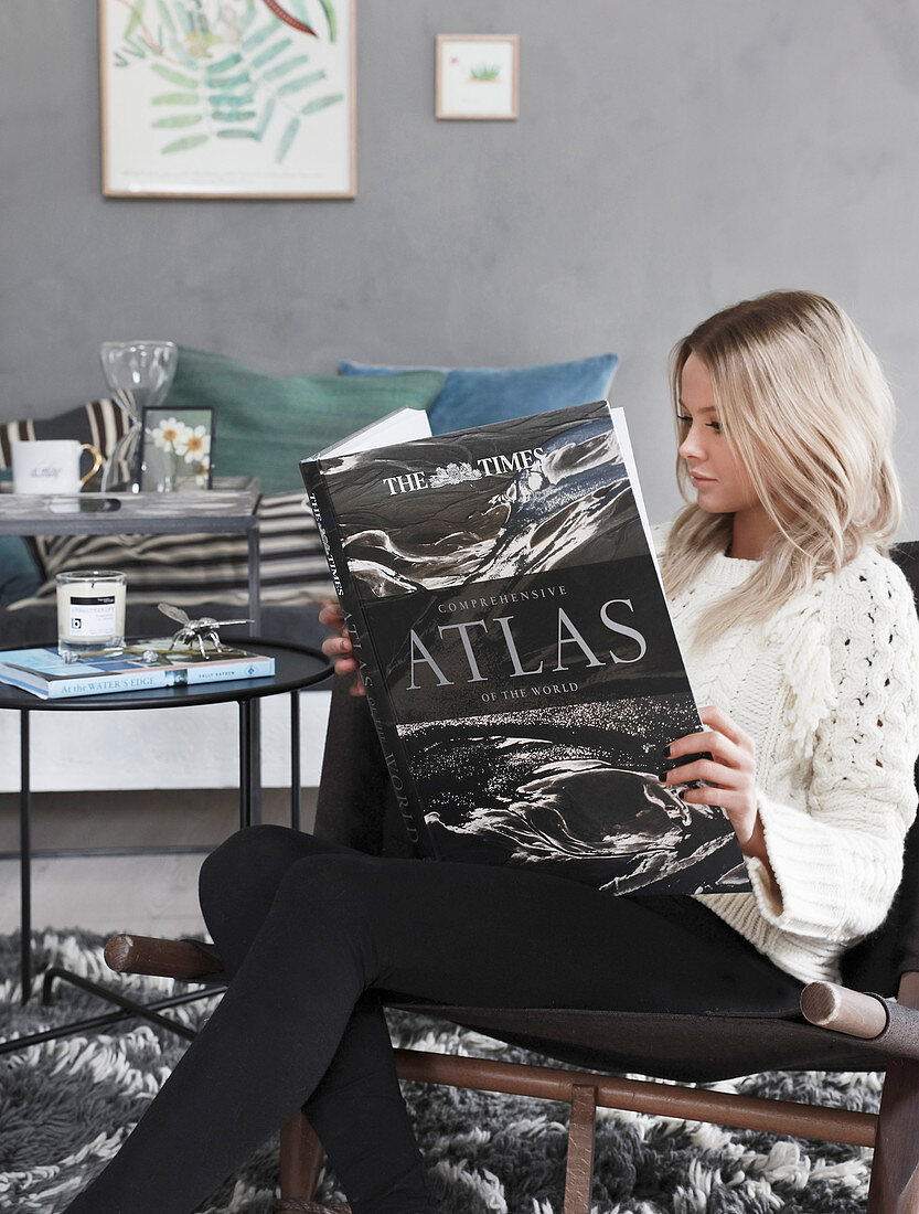 Woman sitting in living room reading atlas