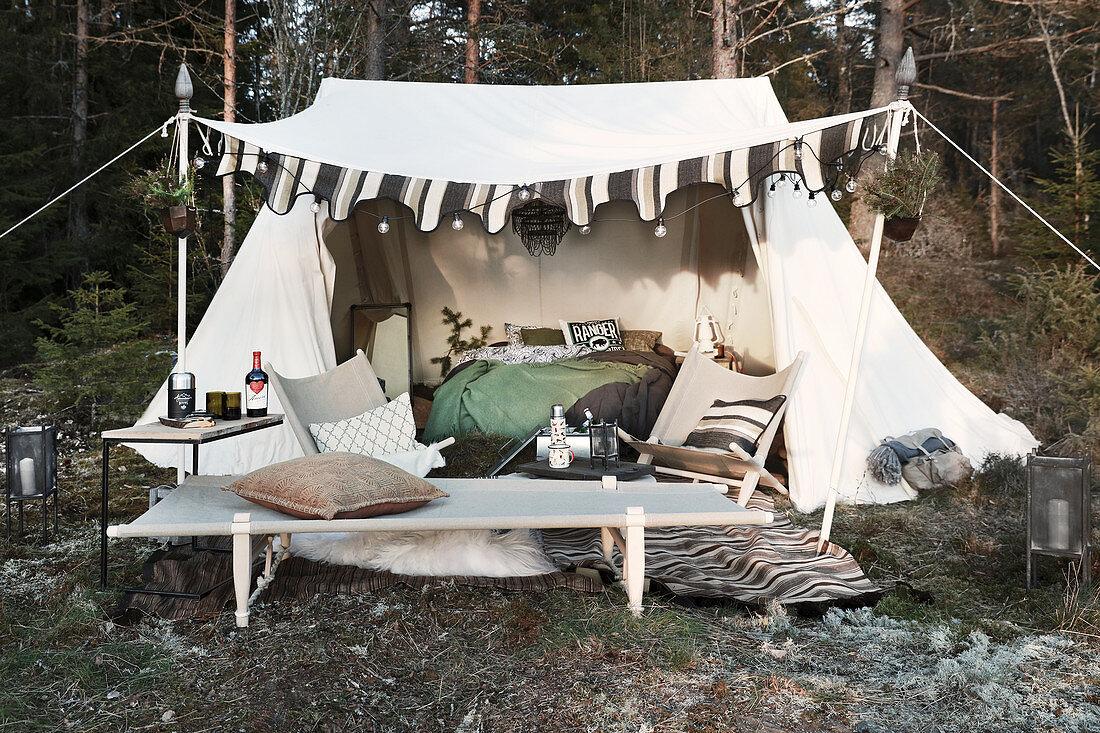 Feldbett und Stühle vor eingerichtetem Zelt mit Lichterkette