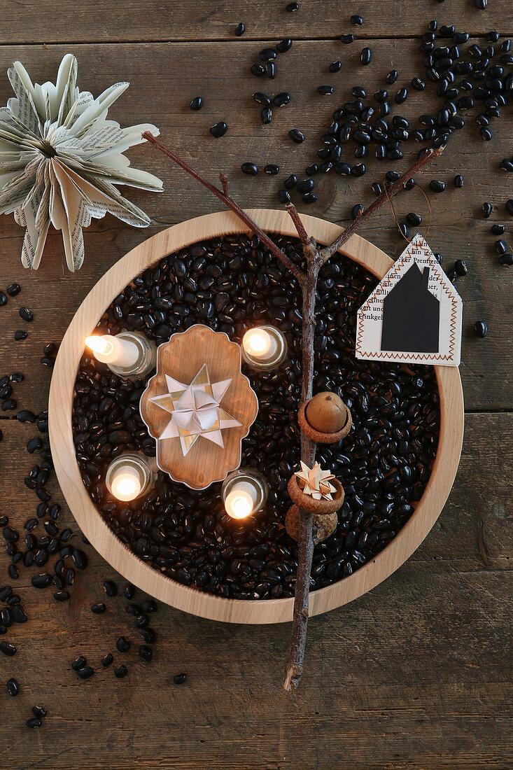 Vier brennende Kerzen im Holzteller mit schwarzen Bohnen als Adventskranz