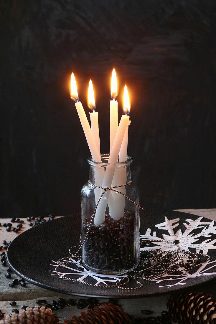 Lit candles in jar of black beans against black background
