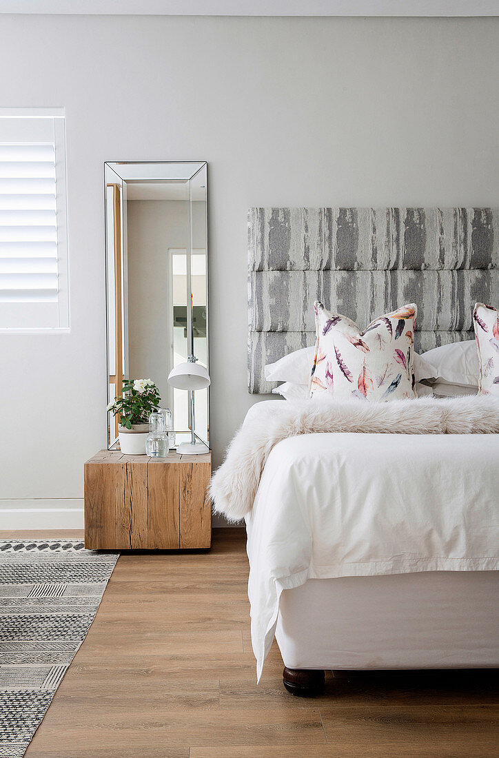 Wooden block used as bedside table below mirror next to bed with upholstered headboard