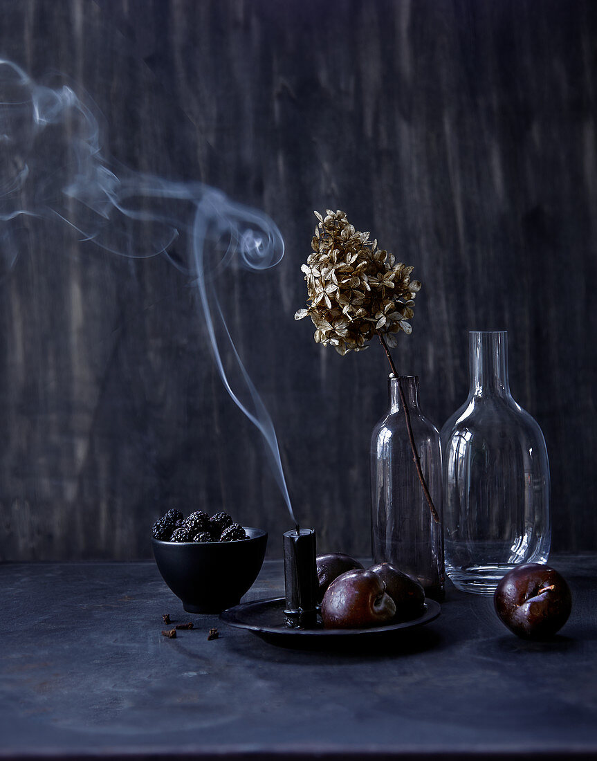 Still-life arrangement of dark fruit, glass bottles and candle smoke