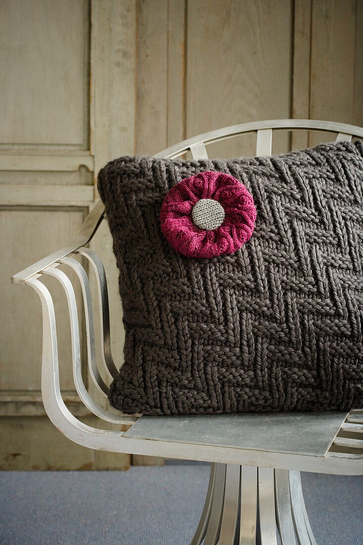 Cushion with knitted cover and knitted flower on chair
