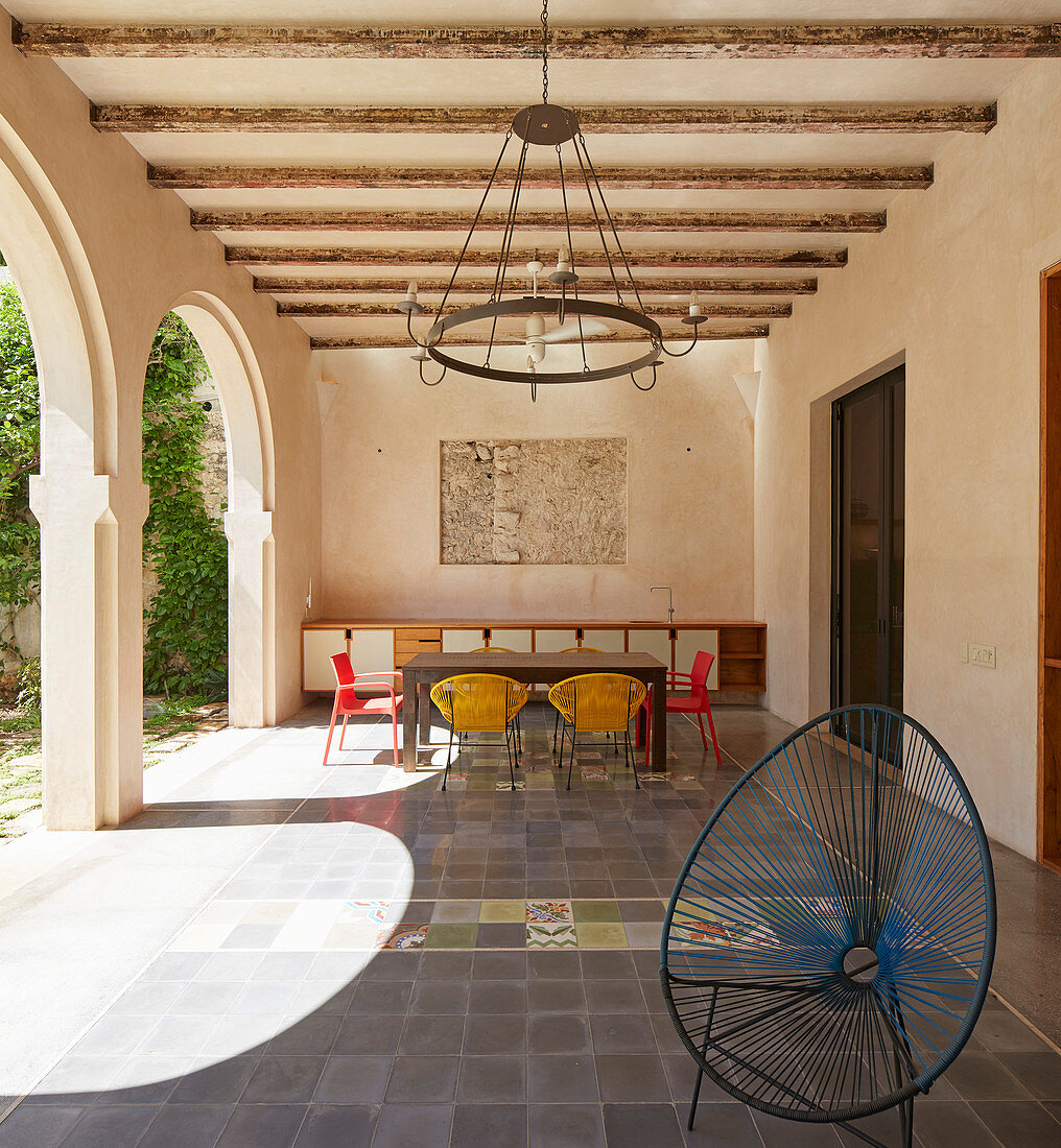 Colourful chairs around table in loggia with tiled floor