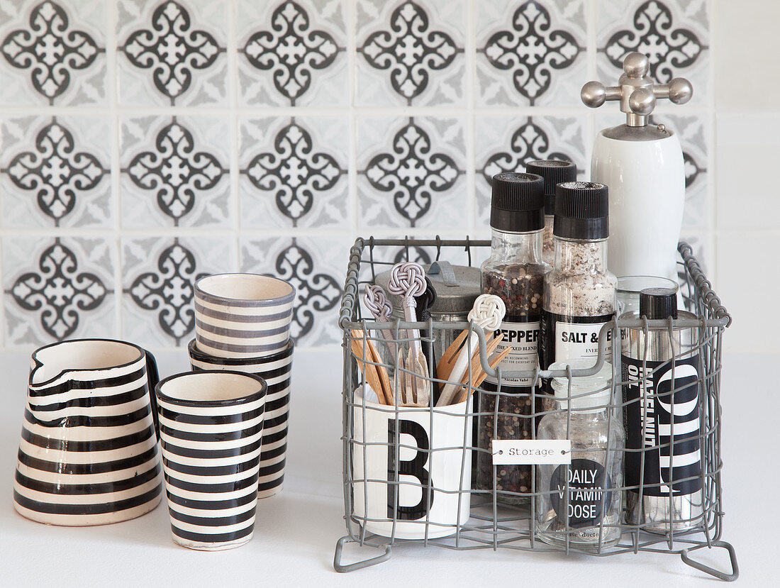 Spices in wire basket next to striped beakers and jug against tiled splashback