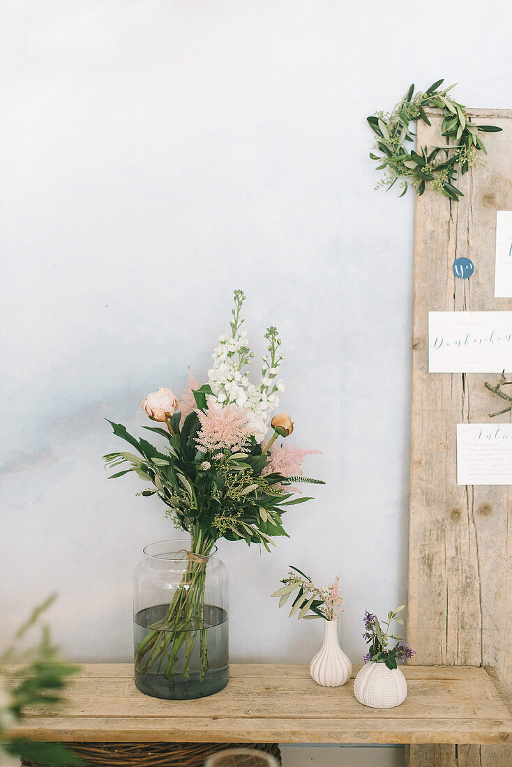 Bouquet of flowers in glass vase on rustic wooden table