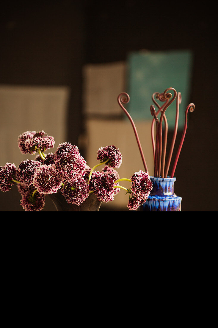 Vases of flowers and fern shoots on table (Mexico)