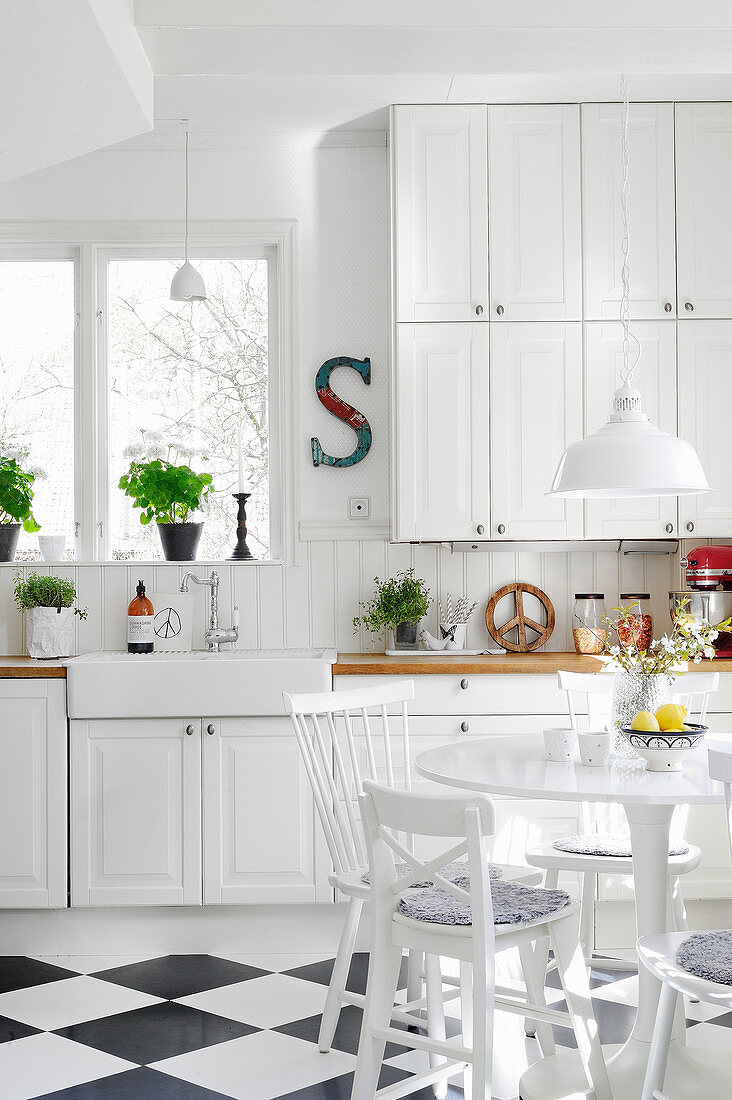 Bright country-house kitchen with chequered floor and dining area