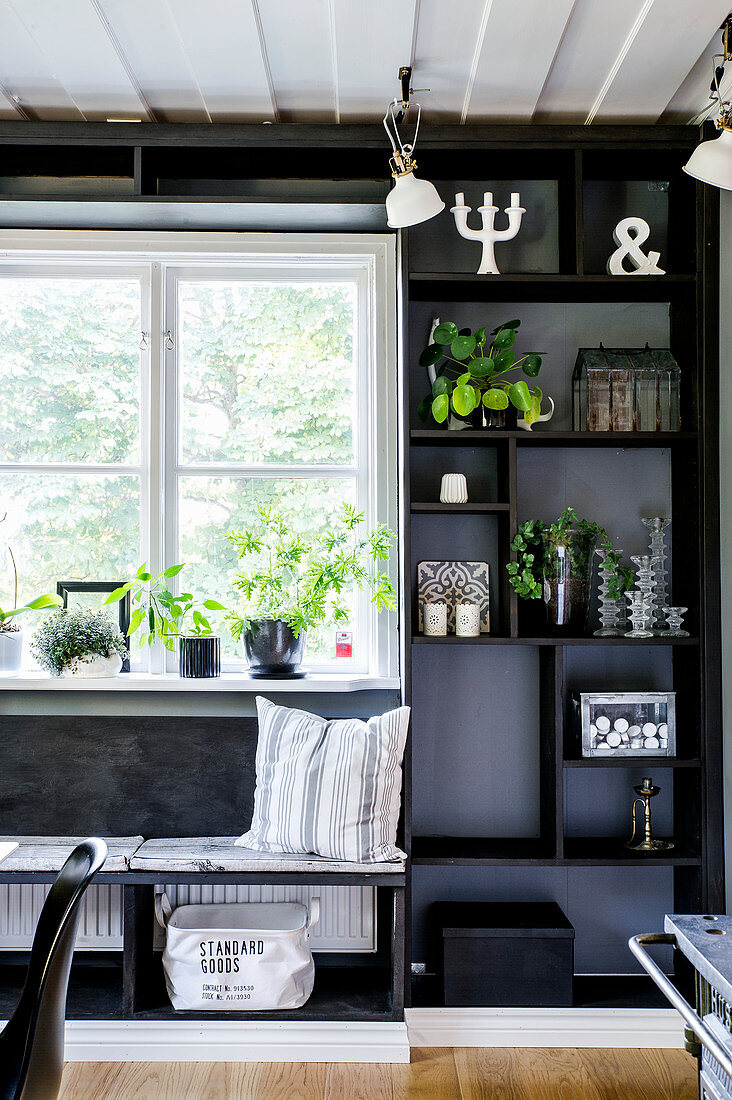 Bench next to black shelves against black wall