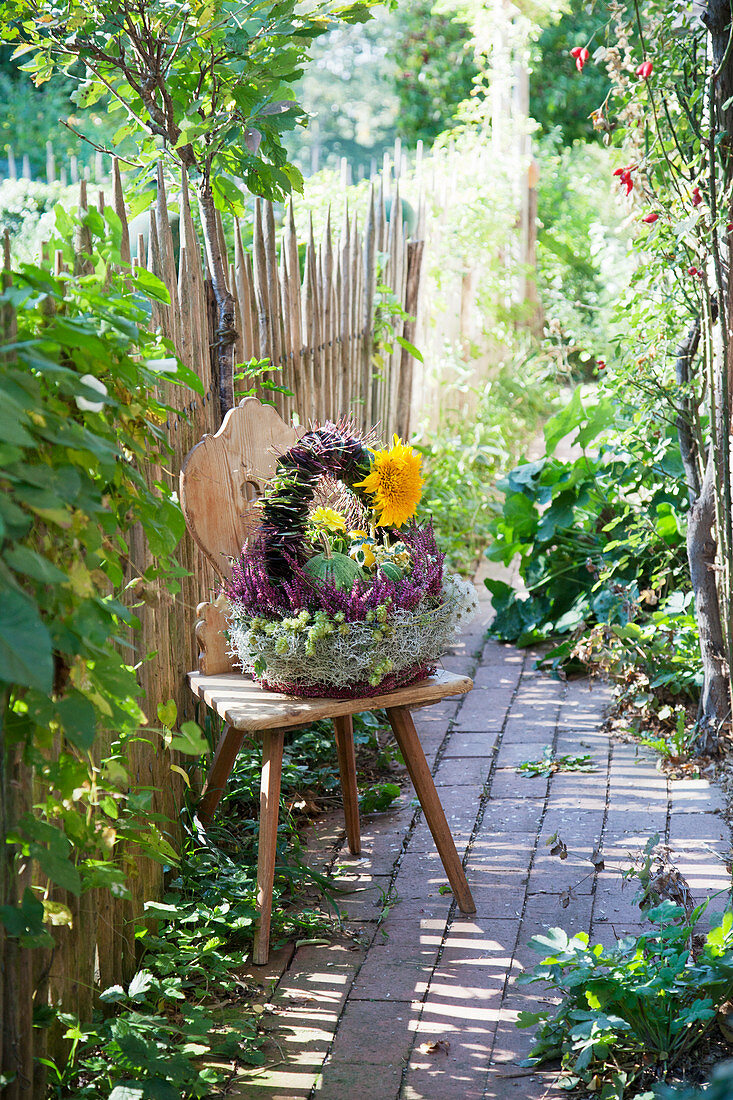 Autumn arrangement in basket with handle on farmhouse chair