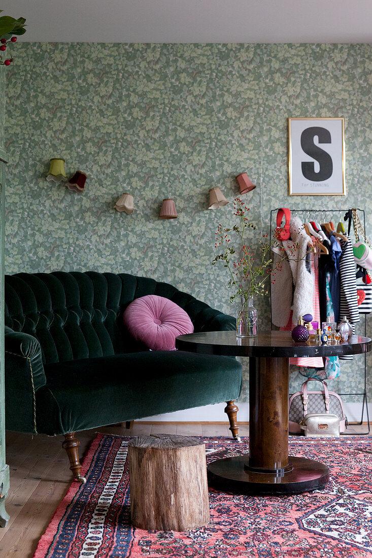 Green velvet sofa, round wooden table and green wallpaper