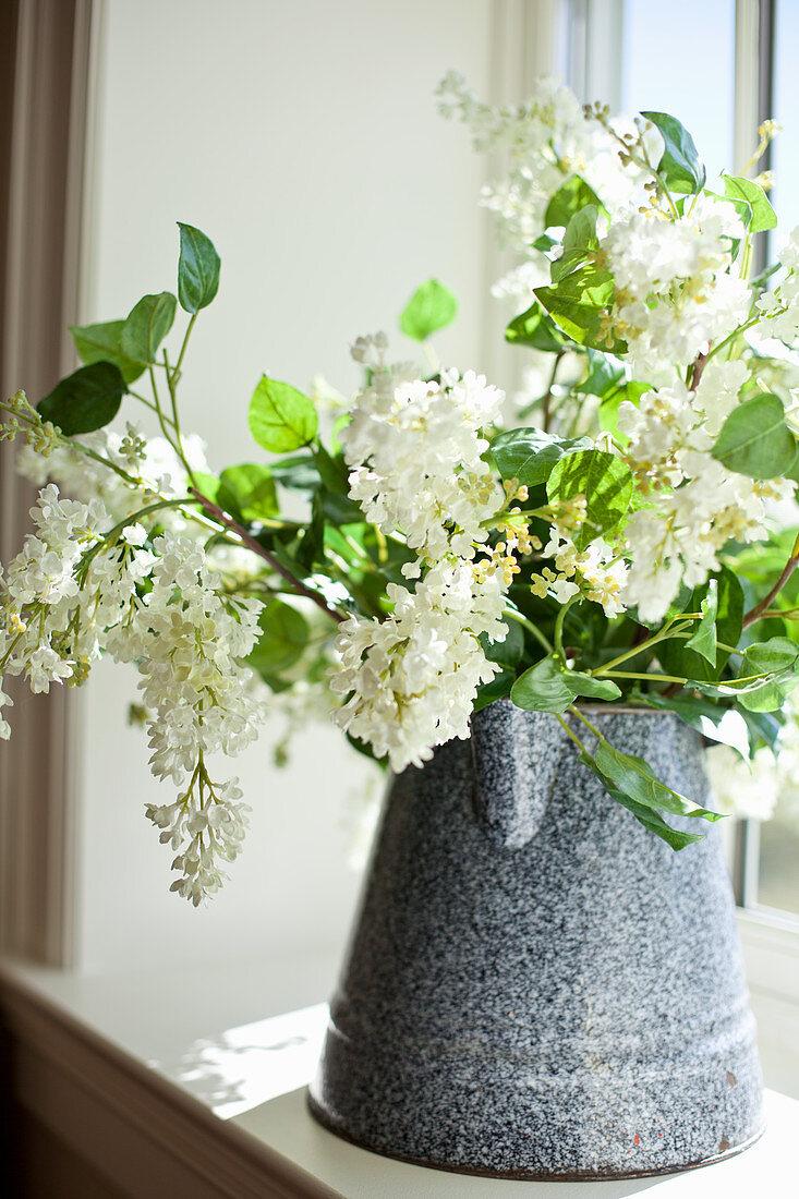 Arrangement of white lilac in old enamel jug on windowsill