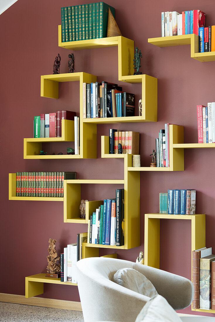 Yellow designer bookshelves on dark red wall