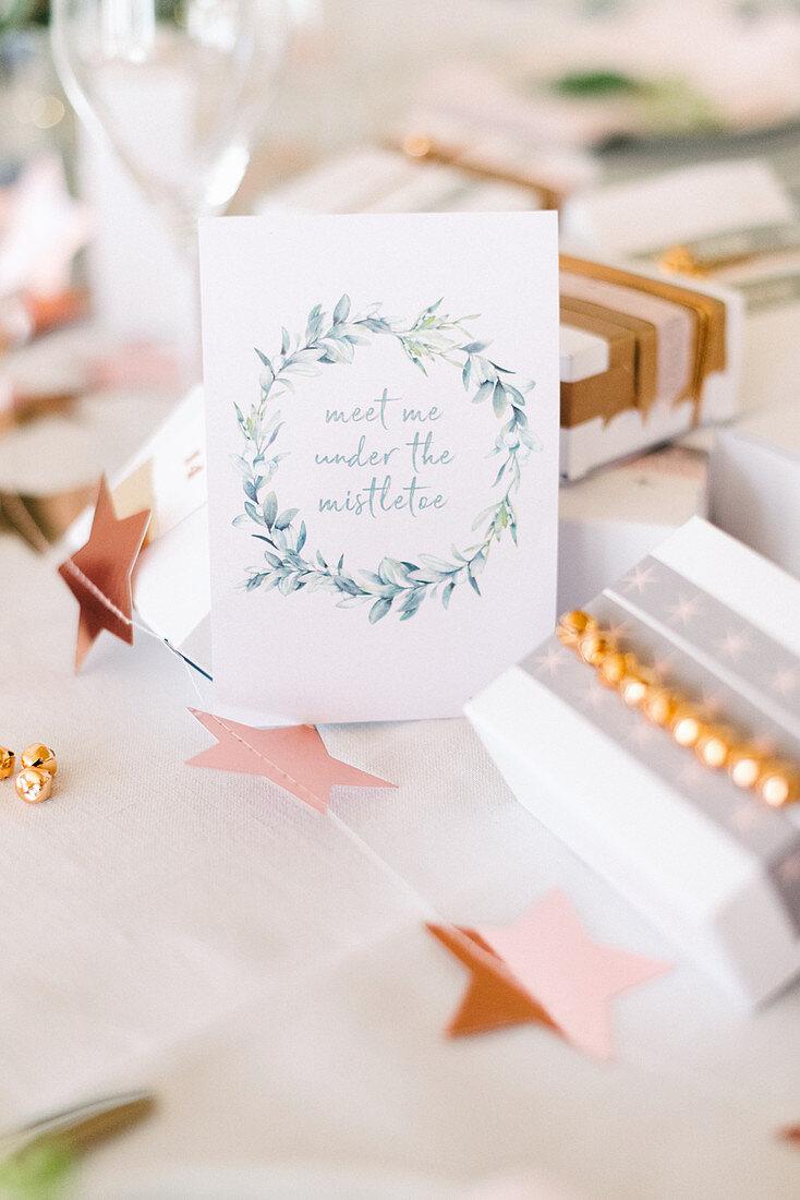 Grußkarte mit Kranz und Handlettering zwischen Geschenken