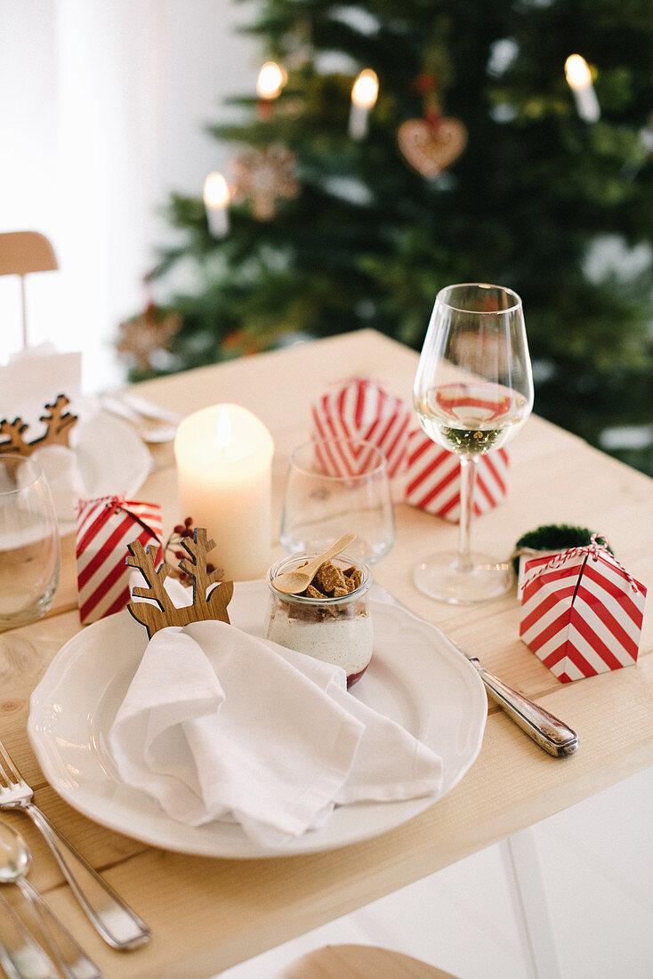 Weihnachtsgedeck mit Spekulatiusmousse im Glas und Gastgeschenk in rot-weiß gestreifter Schachtel