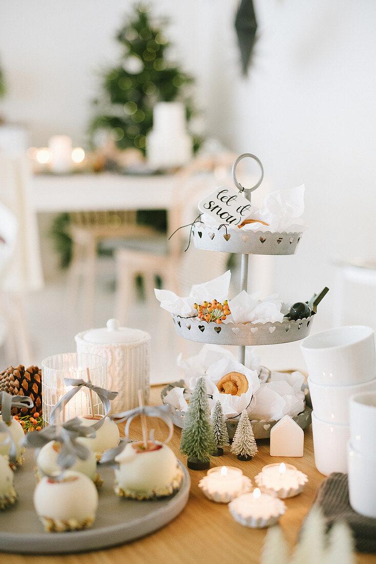 weiße Schokoäpfel, Etagere mit Zimtschnecken und Weihnachtsdeko auf Tisch