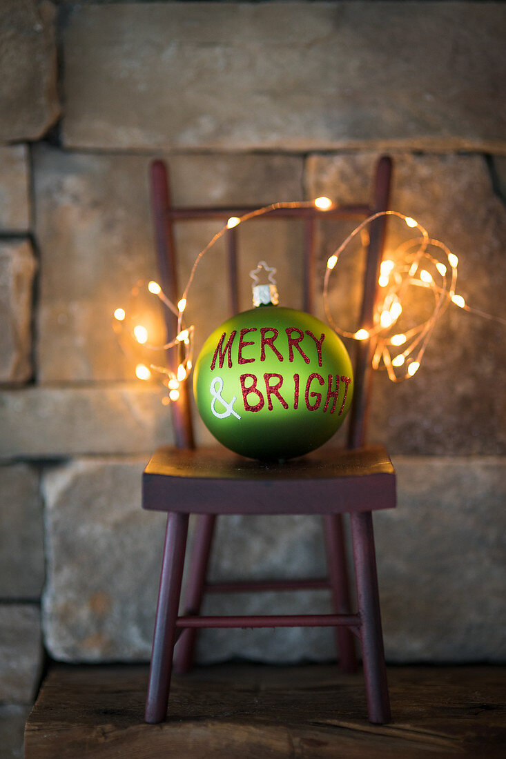 Green Christmas bauble and fairy lights on miniature chair