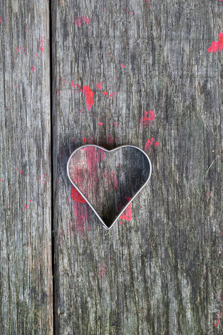 Heart-shaped pastry cutter on wooden surface splattered with red paint