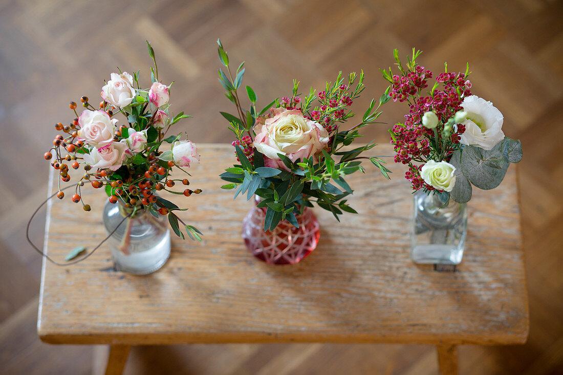 Drei kleine Blumensträuße in Vasen auf einem alten Holzschemel