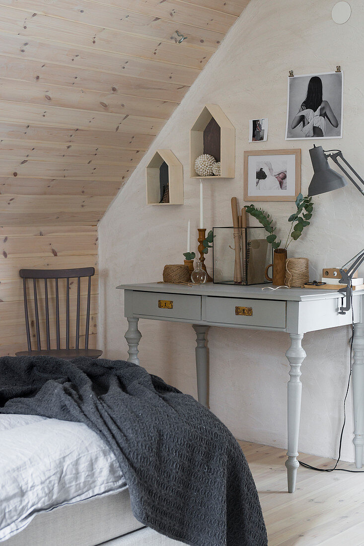 Ornaments in natural shades above grey desk in bedroom