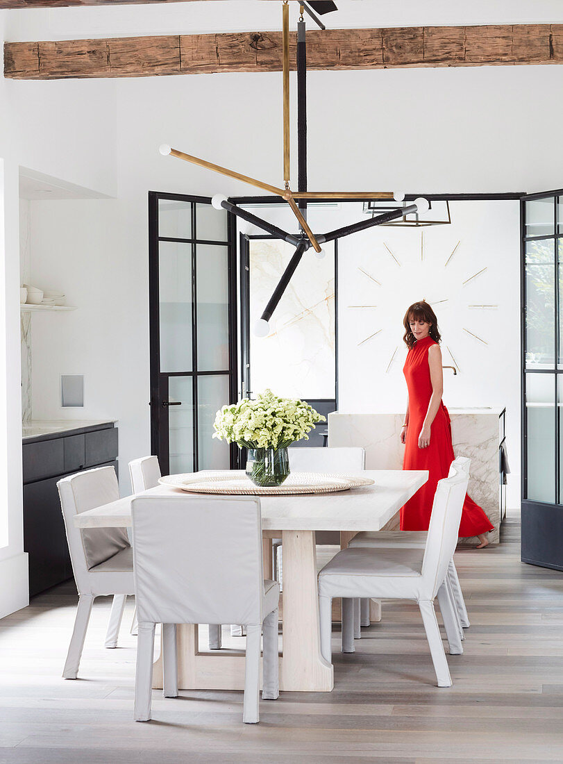 Dining area with designer lamps, woman in red dress in background