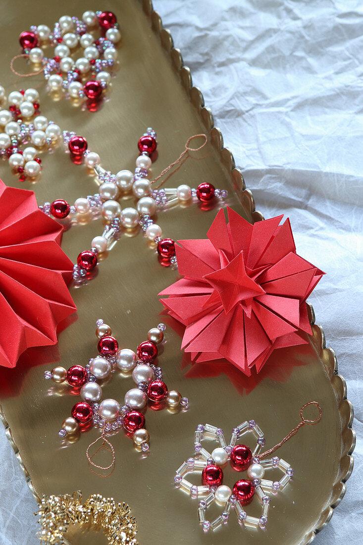 Sterne aus Perlen und gefaltetem Papier auf goldenem Tablett