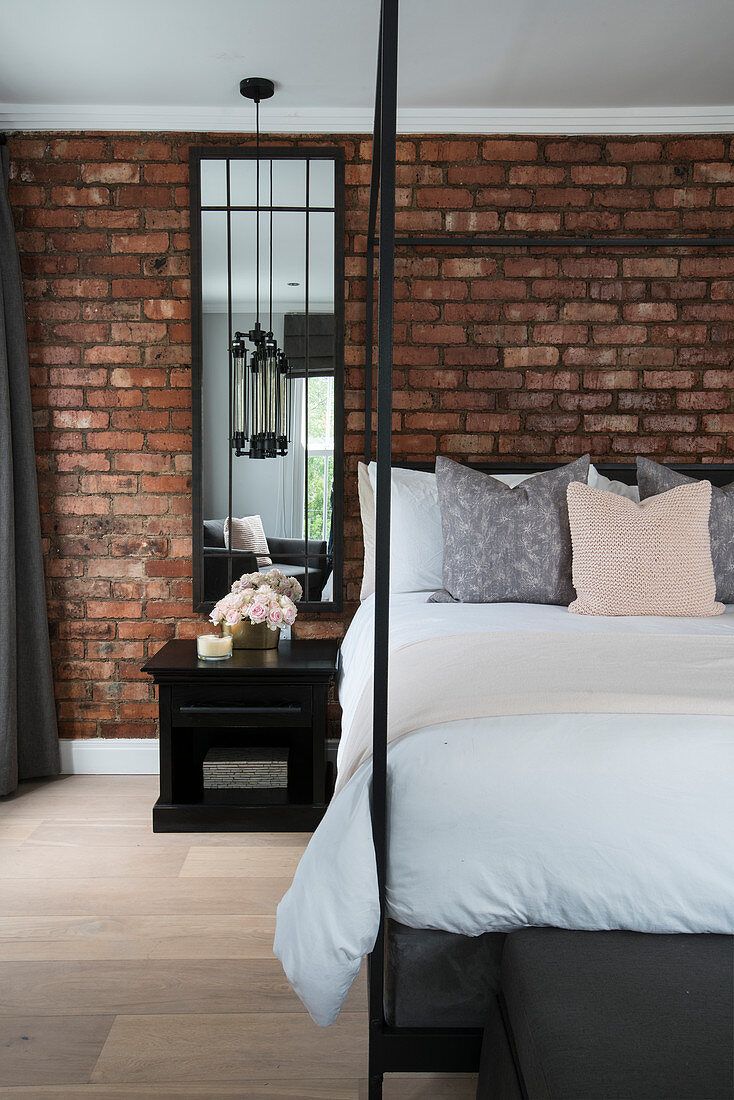 Black four-poster bed in front of exposed brick wall