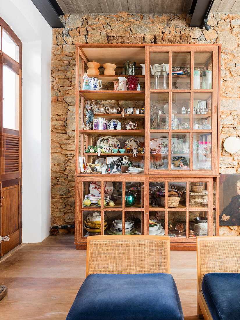 Crockery in rustic glass-fronted cabinet against stone wall