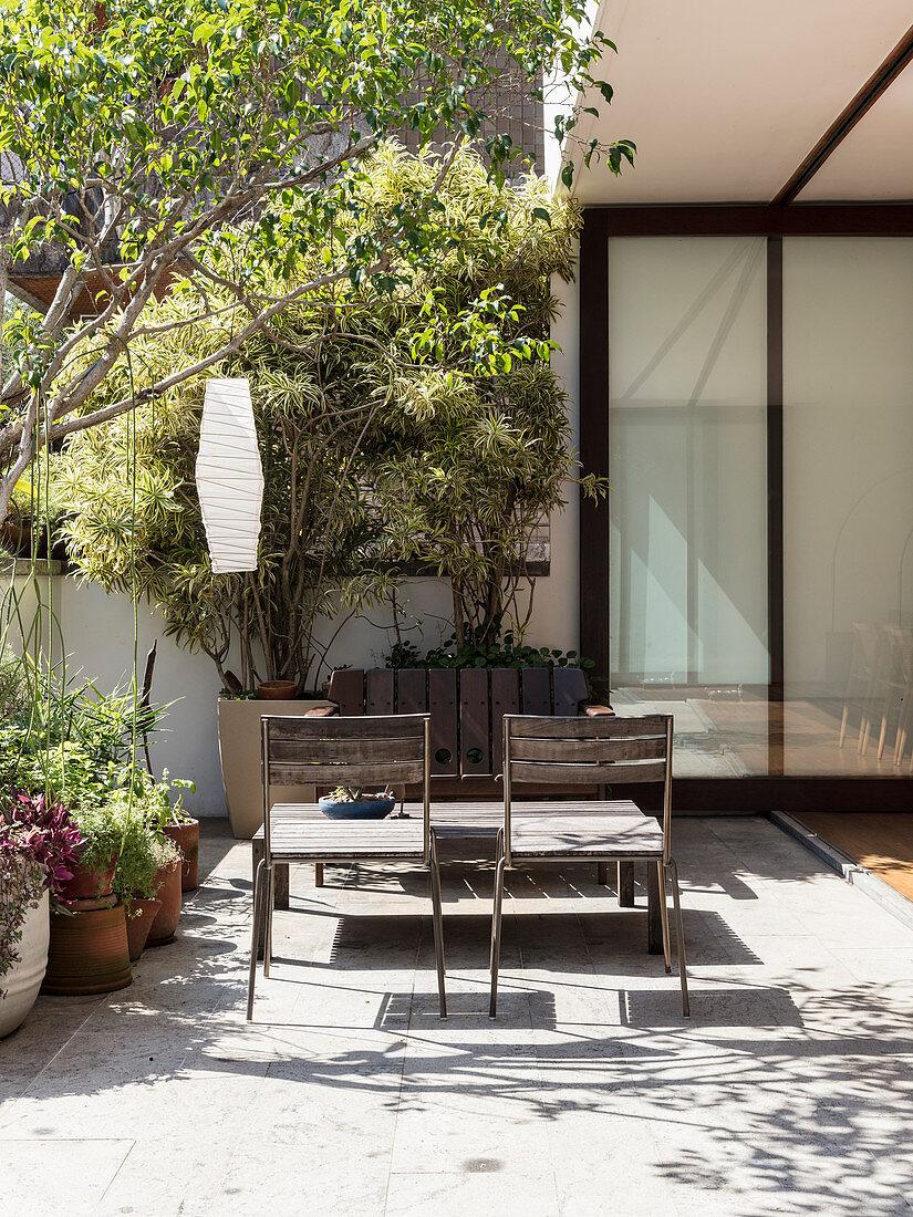 Offene Ziehharmonikatür zur sonnigen Terrasse mit Sitzplatz
