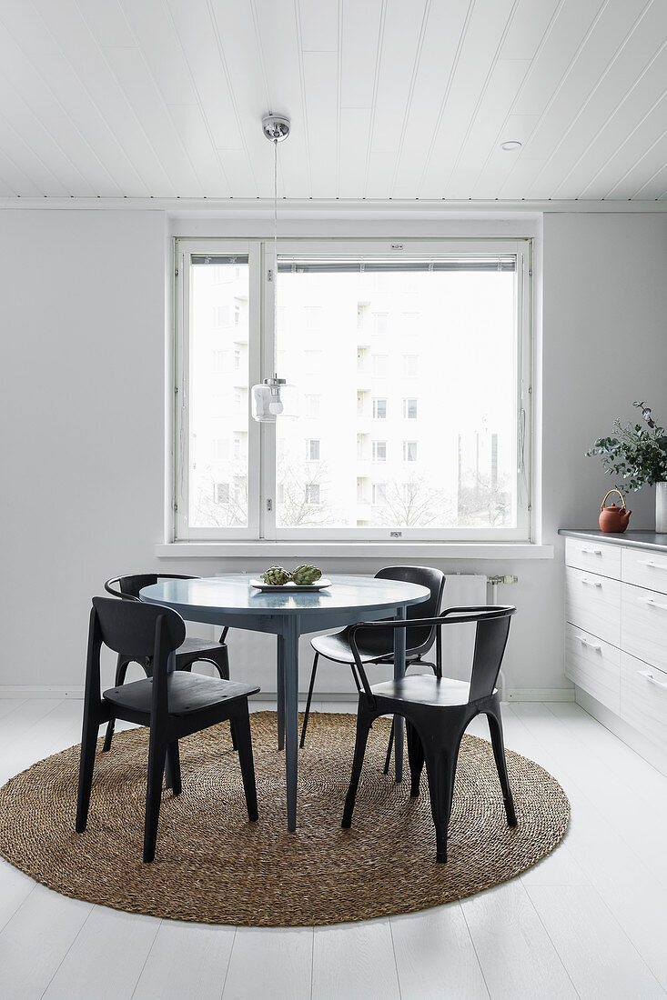 Round table and chairs on round rug next to kitchen counter